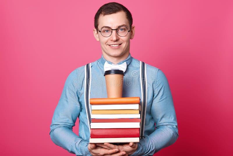Sluit omhoog portret van jonge student in blauw overhemd in één toon, houdt koffie op reusachtige stapel boeken, wil rust en dran stock foto's