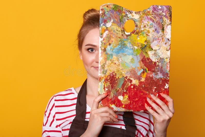 Sluit omhoog portret van jonge vrouwenschilder tegen gele studiomuur, trekt beeld, dame die toevallig gestreept overhemd dragen e stock afbeeldingen