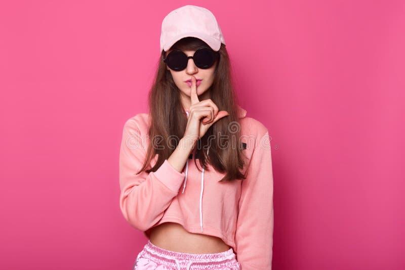 Sluit omhoog portret van Kaukasische mooie slanke jonge meisjestiener in het heldere verkorte hoodie stellen op rooskleurige acht royalty-vrije stock foto