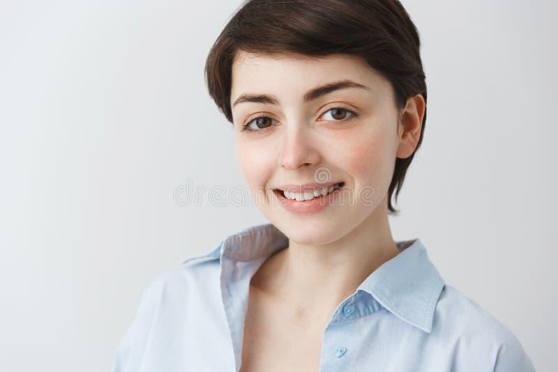 Sluit omhoog portret van knap jong studentenmeisje die met grote bruine ogen, in camera met kijken brightfully glimlachen royalty-vrije stock afbeeldingen
