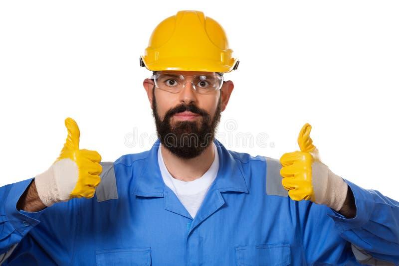 Sluit omhoog portret van knappe gebaarde bouwer die in bouwvakker zijn duimen omhoog in werkende handschoenen, concept succes en  stock afbeelding