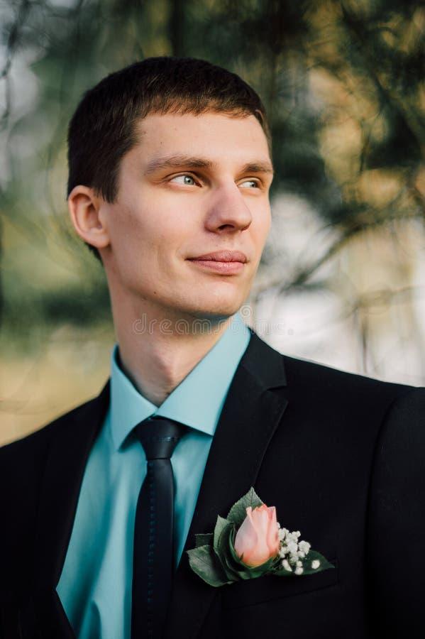 Sluit omhoog portret van knappe modieuze bruidegom in openlucht in park met rode bowtie royalty-vrije stock foto's