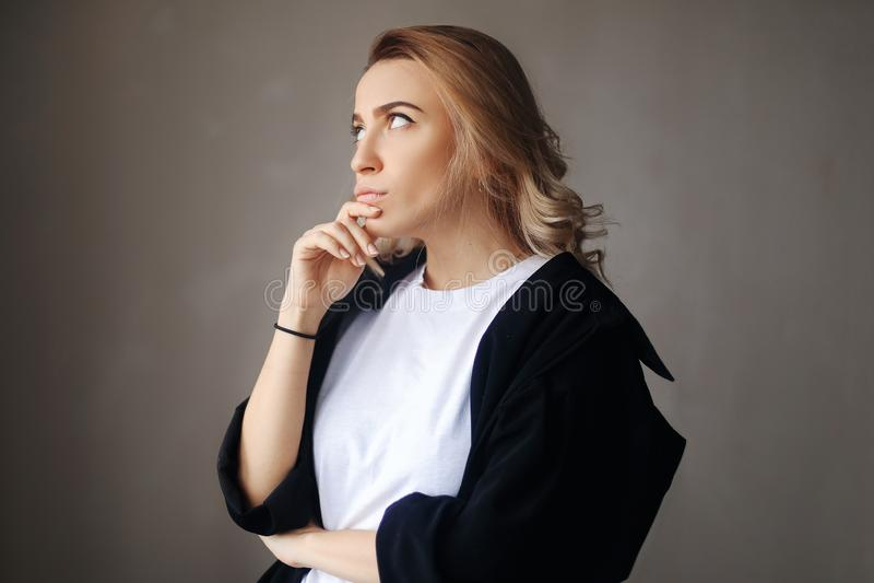 Sluit omhoog portret van krullend blonde zeker nadenkend meisje, die hand houden dichtbij het gezicht royalty-vrije stock foto
