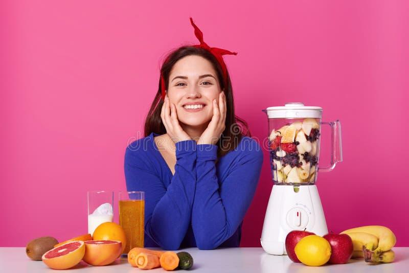 Sluit omhoog portret van leuke glimlachende jonge vrouw met gelukkige uitdrukking, houdt haar handen op wangen die, in fotostudio stock foto