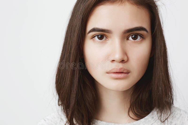Sluit omhoog portret van leuke tiener met ernstige en geconcentreerde uitdrukking, over witte achtergrond aantrekkelijk royalty-vrije stock afbeelding