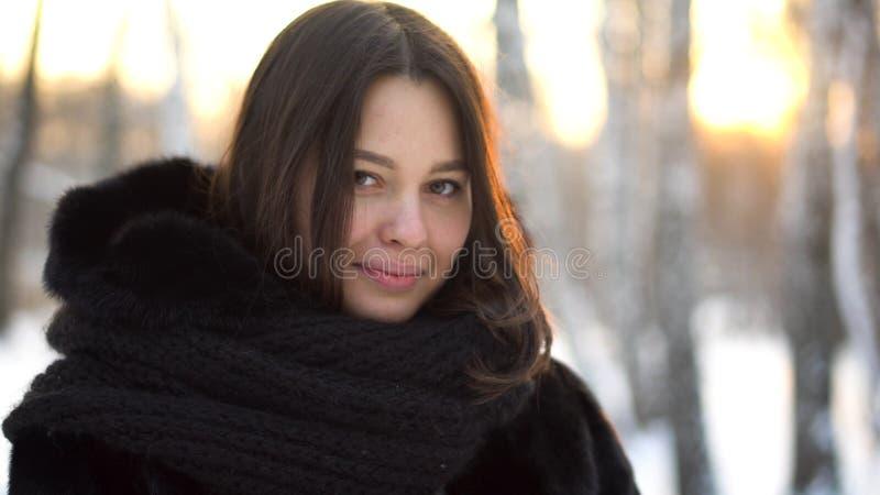 Sluit omhoog portret van mooi donkerbruin meisje in zwarte bontjas en grote, gebreide sjaal openlucht in het bos van de de winter stock fotografie