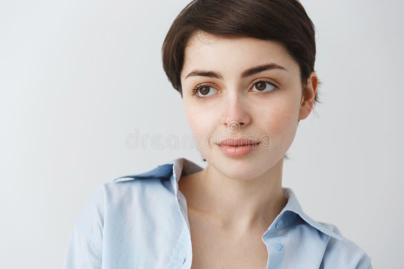 Sluit omhoog portret van mooi Kaukasisch meisje die met kort donker haar en grote bruine ogen, zacht glimlachen met opzij kijken stock fotografie