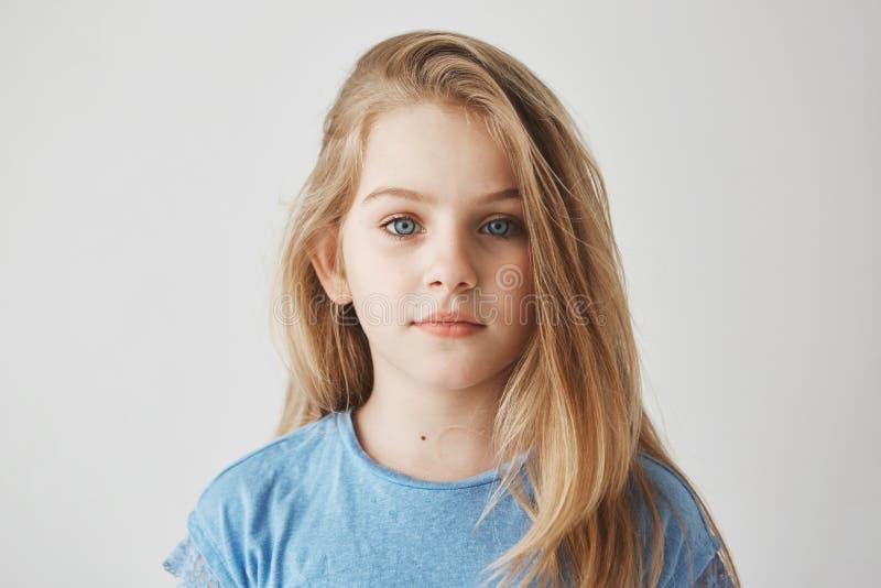Sluit omhoog portret van mooi meisje die met licht lang haar en grote blauwe ogen in camera met ontspannen kijken royalty-vrije stock afbeelding