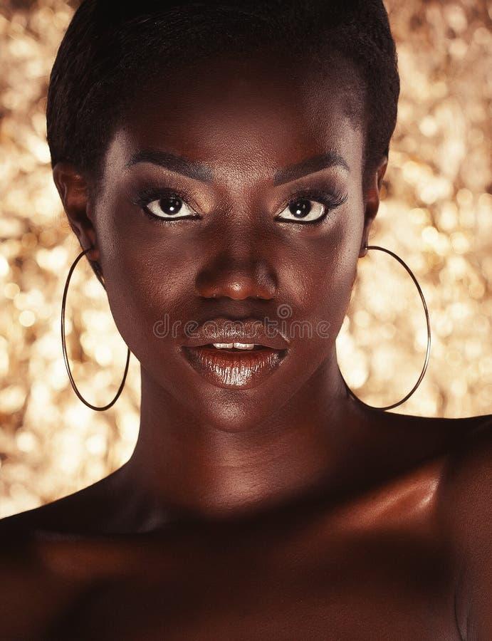 Sluit omhoog portret van mooie Afrikaanse vrouw met creatief goud omhoog maken royalty-vrije stock foto