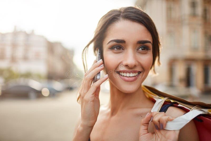 Sluit omhoog portret van mooie blije jonge Kaukasische vrouw die met donker haar met tanden glimlachen, opzij met gelukkig kijken royalty-vrije stock afbeelding