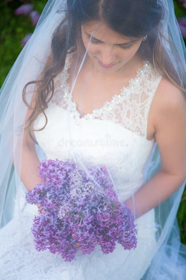 Sluit omhoog portret van mooie bruid met lilac bloemen royalty-vrije stock afbeeldingen