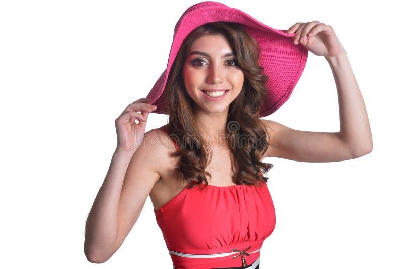Sluit omhoog portret van mooie donkerbruine jonge vrouw in roze hoed op witte achtergrond stock afbeelding