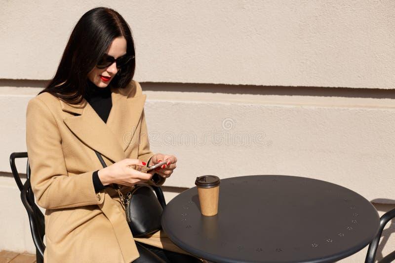 Sluit omhoog portret van mooie elegante jonge vrouw die beige laag dragen en meeneemkoffie drinken terwijl het hebben van lunchti royalty-vrije stock foto