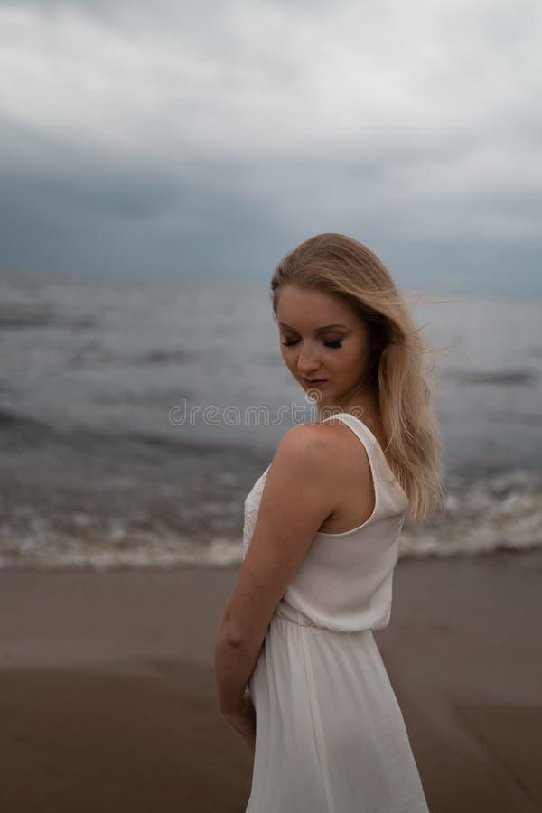 Sluit omhoog portret van mooie jonge het strandnimf van de blondevrouw in witte kleding dichtbij overzees met golven tijdens saai royalty-vrije stock foto's