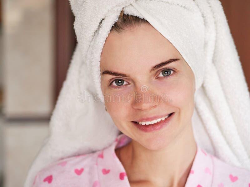 Sluit omhoog portret van mooie jonge vrouw in handdoektulband na ochtenddouche het stellen in badkamers voor venster stock afbeeldingen