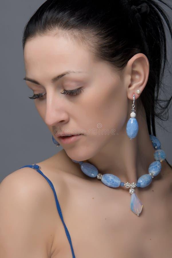 Portret van mooie donkerbruine vrouw die charmante levendige juwelen dragen stock afbeelding