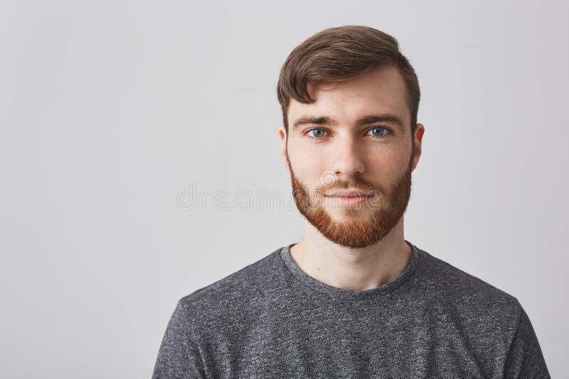 Sluit omhoog portret van mooie mannelijke gebaarde kerel met modieus kapsel glimlachend, kijkend in camera met gelukkig en kalm stock afbeelding