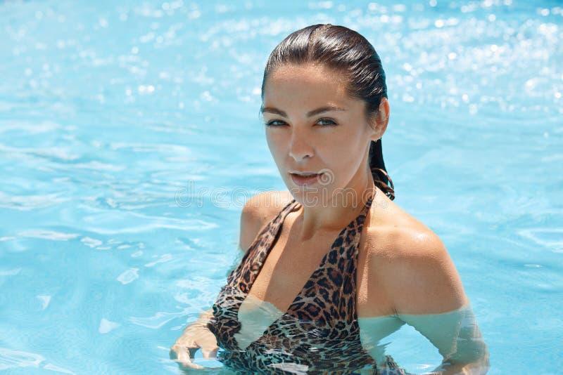 Sluit omhoog portret van mooie vrouw die zich in pool die in duidelijk blauw water bevinden, direct camera, gekleed in zwemmend k stock fotografie