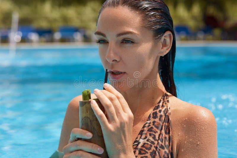 Sluit omhoog portret van nadenkend magnetisch donkerbruin model die zich in zwembad bevinden, die container met de zomercocktail  stock foto's