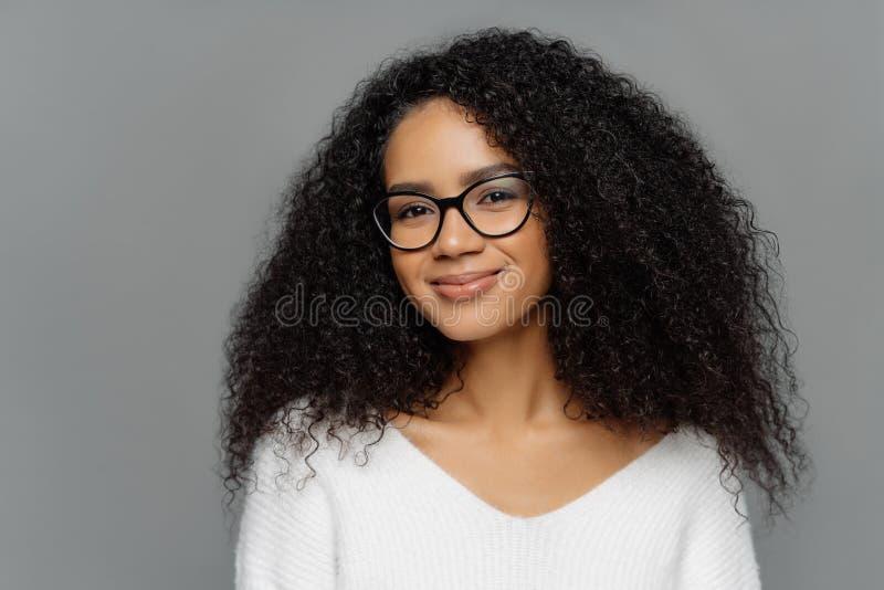 Sluit omhoog portret van opgetogen mooie Afro-vrouw met dichtbegroeid krullend haar, kijkt door transparante glazen, draagt witte stock afbeeldingen