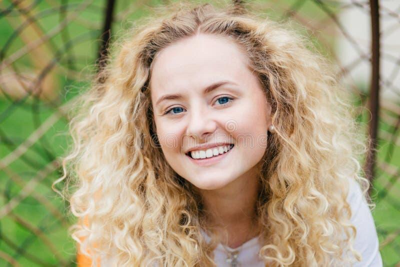 Sluit omhoog portret van romantisch mooi eerlijk haired wijfje met aantrekkelijke glimlach, openlucht rust die, in goede stemming stock foto's