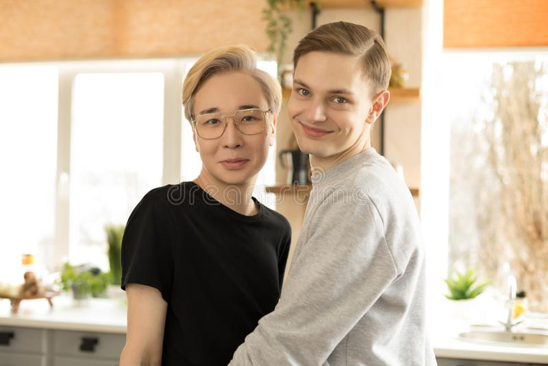Sluit omhoog portret van twee jonge internationale homoseksuelen in vrijetijdskleding, één Aziatische blondemensen in oogglazen royalty-vrije stock afbeelding