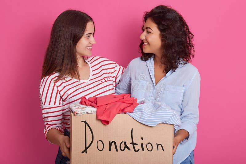 Sluit omhoog portret van twee meisjes die, vrouwen die doos met kleren voor armen houden, aantrekkelijk wijfje die schenking make royalty-vrije stock fotografie