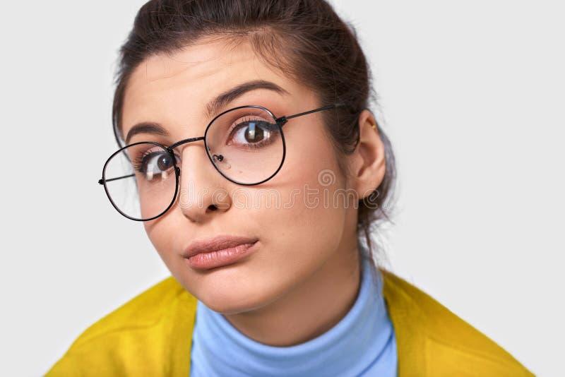 Sluit omhoog portret van twijfelachtige jonge vrouw met een broodjeskapsel, die toevallige uitrusting en ronde transparante bril  stock afbeelding