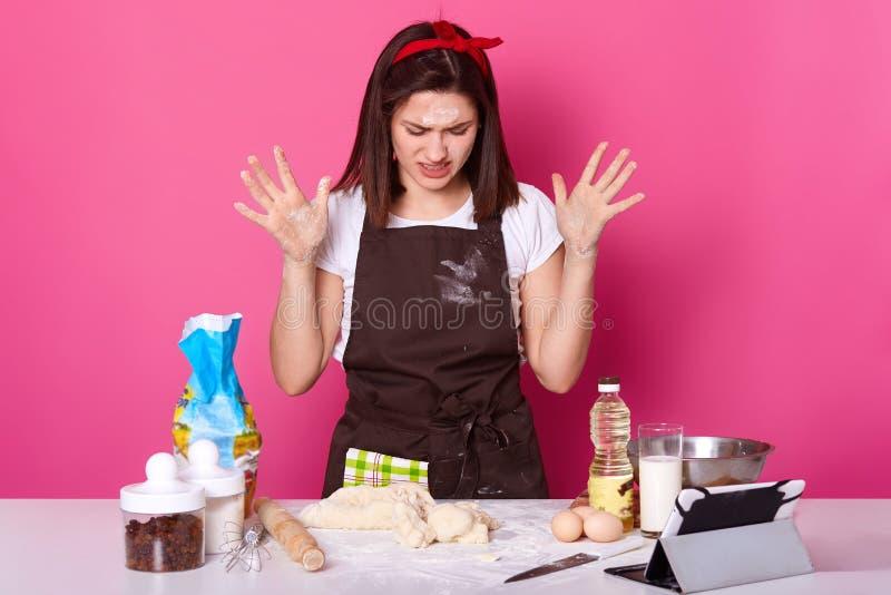 Sluit omhoog portret van vermoeide huisvrouw of de bakker kijkt droevig, brengt partijenuren door voorbereidend Pasen-cake heeft, stock afbeelding