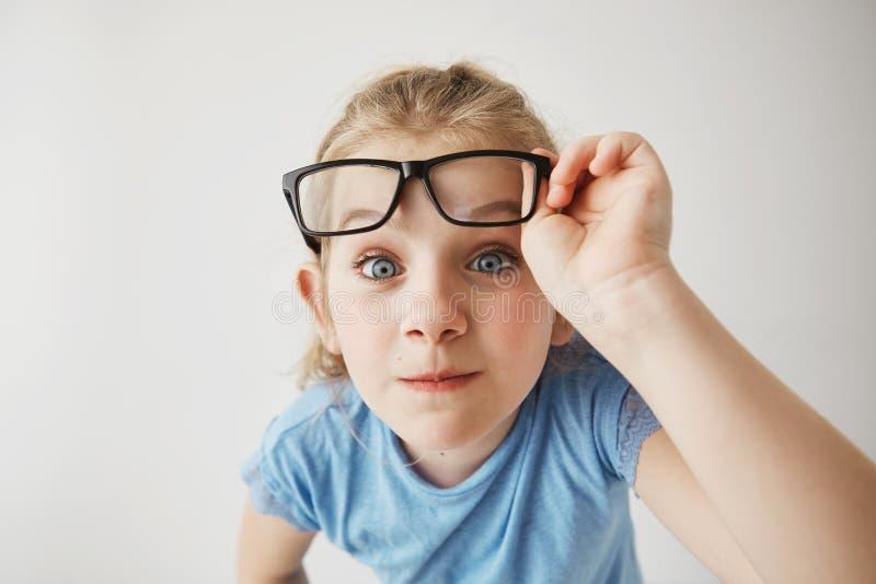 Sluit omhoog portret van vrolijk klein meisje met blondehaar en de blauwe grappige ogen imiteert volwassen persoon met glazen met stock foto's