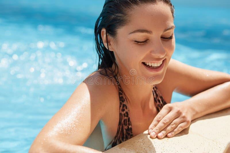Sluit omhoog portret van vrolijk knap brunette zwemmend in schoon water, die rust hebben bij zwembad, die oprecht glimlachen, stock foto