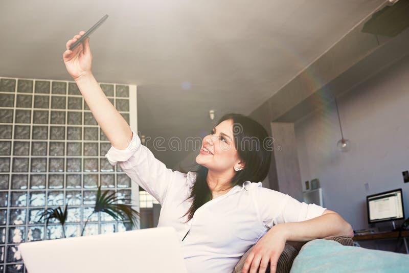 Sluit omhoog portret van vrolijke donkerbruine jonge vrouw die in wit overhemd zelfbeeldzitting op de bank in woonkamer maken royalty-vrije stock foto