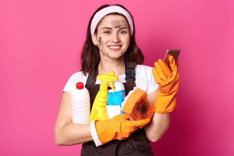 Sluit omhoog portret van vrolijke zoete schoonmaakster in witte toevallige t-shirt, bruine schort en de haarband, houdt spons, te stock foto