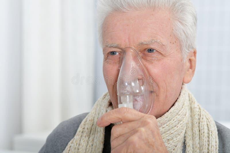 Sluit omhoog portret van ziek hoger mensenportret met inhaleertoestel stock foto's