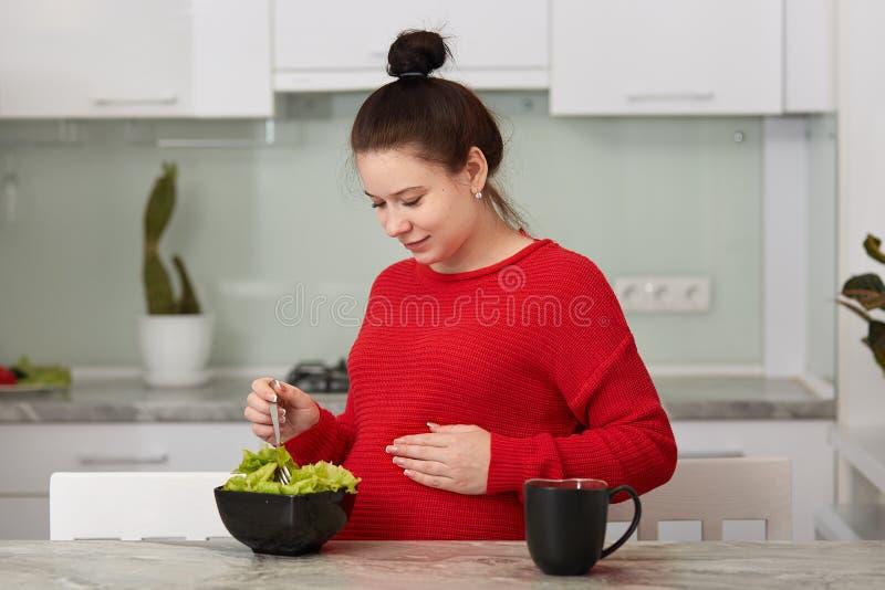 Sluit omhoog portret van zwangere vrouw die verse groene salade in keuken koken, etend vele verschillende groenten tijdens zwange stock foto