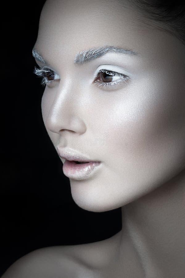 Sluit omhoog profielportret van een jonge vrouw, met artistieke make-up, op een zwarte backgorund Creatief concept stock afbeelding