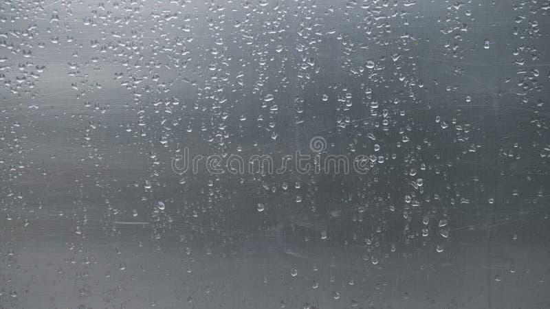 Sluit omhoog regendalingen op het gekraste blad van het aluminiummetaal stock afbeeldingen