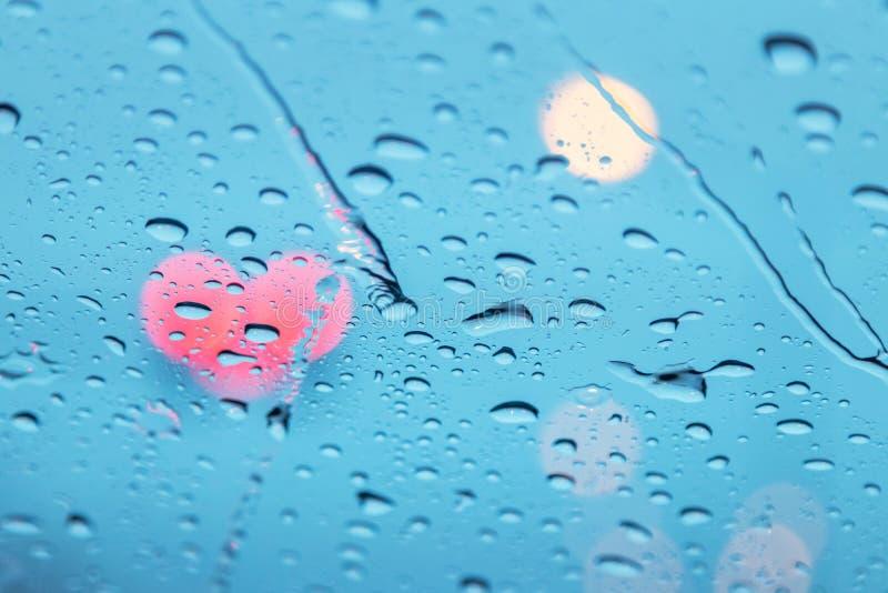 Sluit omhoog regendruppels op de auto van oppervlakteglazen met het hartvorm van het lichtenverkeer bokeh stock afbeeldingen