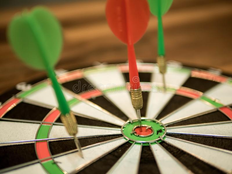 Sluit omhoog rode pijltjepijl die in het doelcentrum raken van dartboard, metafoor aan doelsucces, winnaarconcept royalty-vrije stock foto