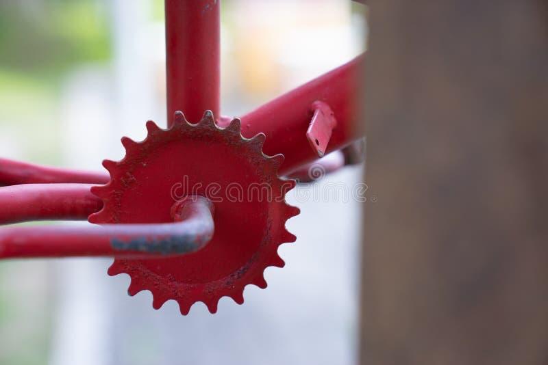 Sluit omhoog rode uitstekende roestig freewheelen van fiets stock fotografie