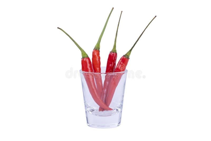 Sluit omhoog roodgloeiende Spaanse peperspeper in een duidelijk glas op geïsoleerde witte achtergrond, concentreer het stapelen e stock foto