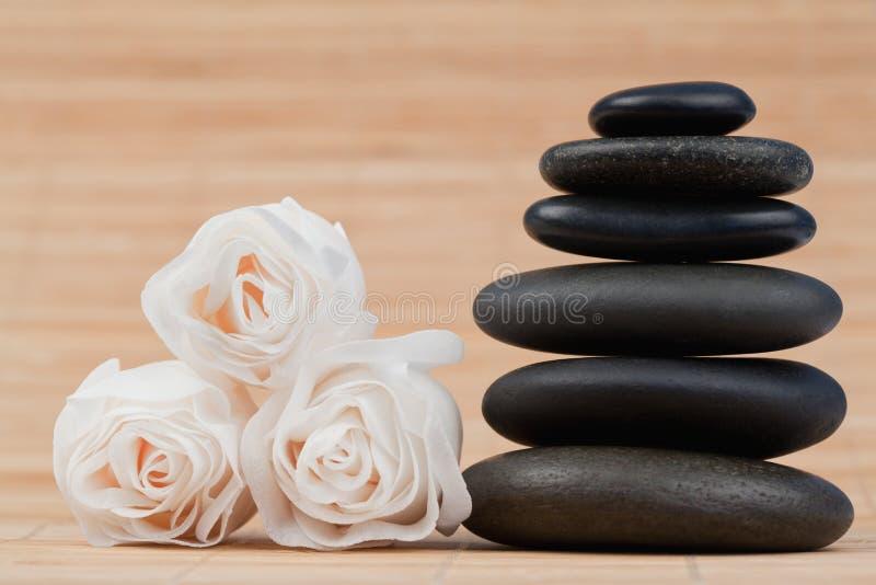 Sluit omhoog rozen en een zwarte kiezelstenenstapel stock foto's