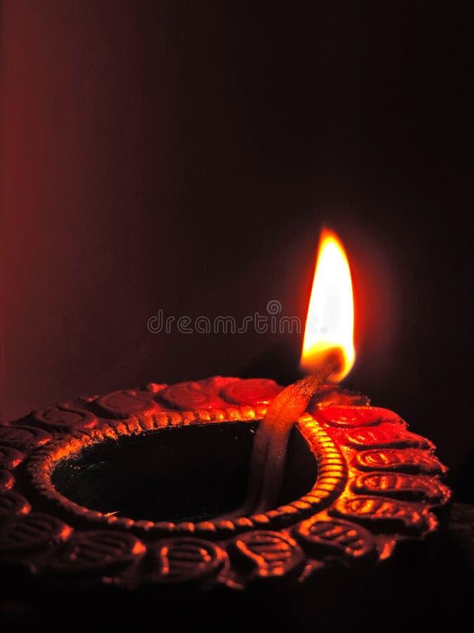 Sluit omhoog rustige de kleilamp van de diwaliolie, chirag of panti op een donkeroranje zwarte achtergrond met heldere oranjerode royalty-vrije stock foto's