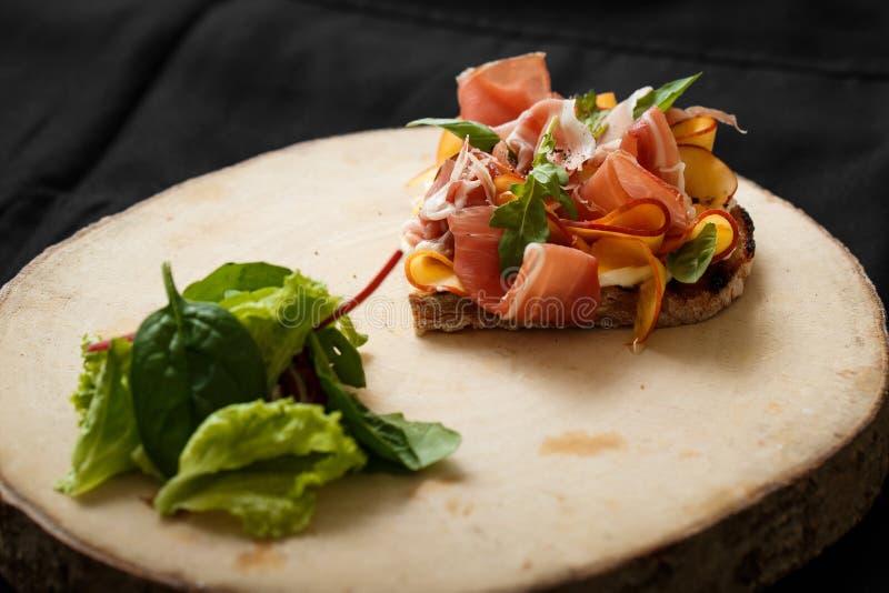 Sluit omhoog sandwich met jamon en salade aan boord stock foto