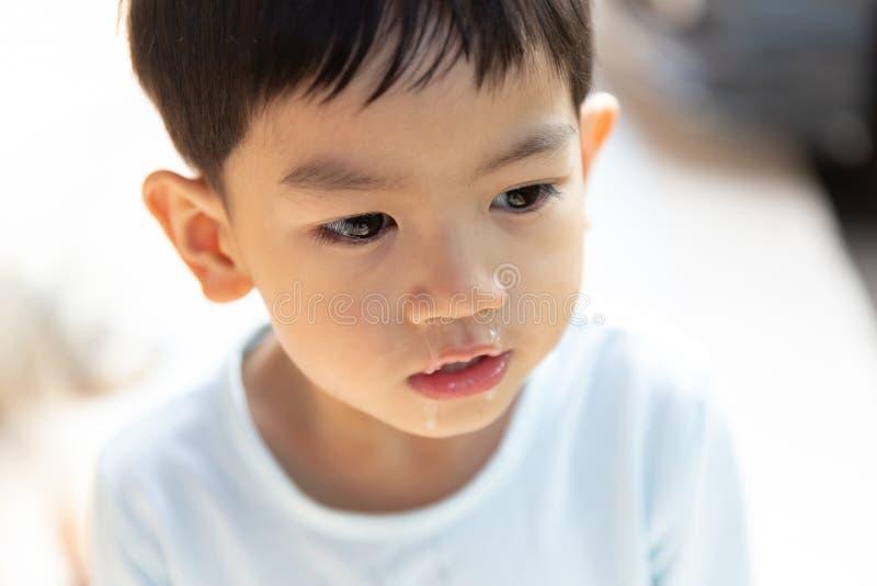 Sluit omhoog slijm die van neus stromen, heeft de Aziatische jongen een lopende neus met duidelijk snot royalty-vrije stock afbeelding