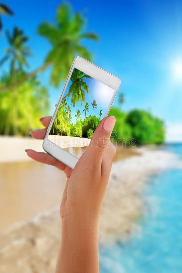 Sluit omhoog smartphone van de handholding op de zomerstrand technologie, reis, toerisme, mededeling en mensenconcept royalty-vrije stock fotografie