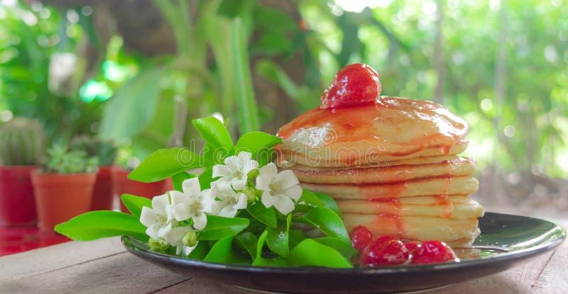 Sluit omhoog stapel van pannekoek, eigengemaakt dessert gediend op zwarte plaat met witte bloemen en groene bladeren, zoet desser stock foto's