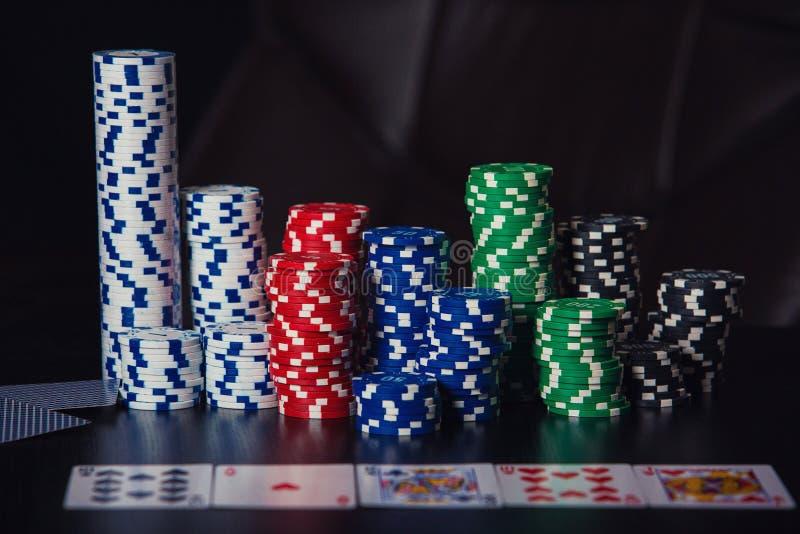 Sluit omhoog stapel verschillende gekleurde die pookspaanders en speelkaarten op de casinolijst over zwarte achtergrond wordt geï stock afbeeldingen