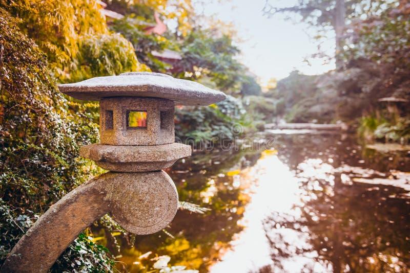 Sluit omhoog steenlantaarn in Japanse stijltuin met vijver en de herfstbomen De traditionele architectuur van Japan Buitenontwerp royalty-vrije stock afbeeldingen