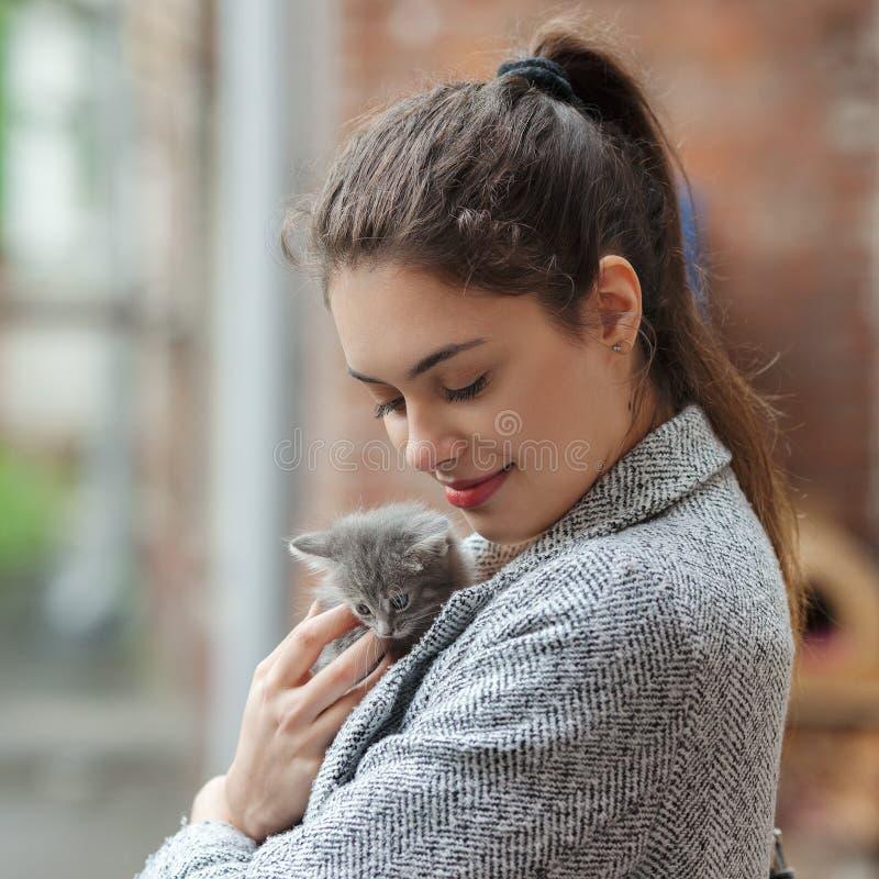 Sluit omhoog straatportret van mooie jonge donkerbruine vrouw in grijze laag met grijs gestreepte katkatje royalty-vrije stock foto's